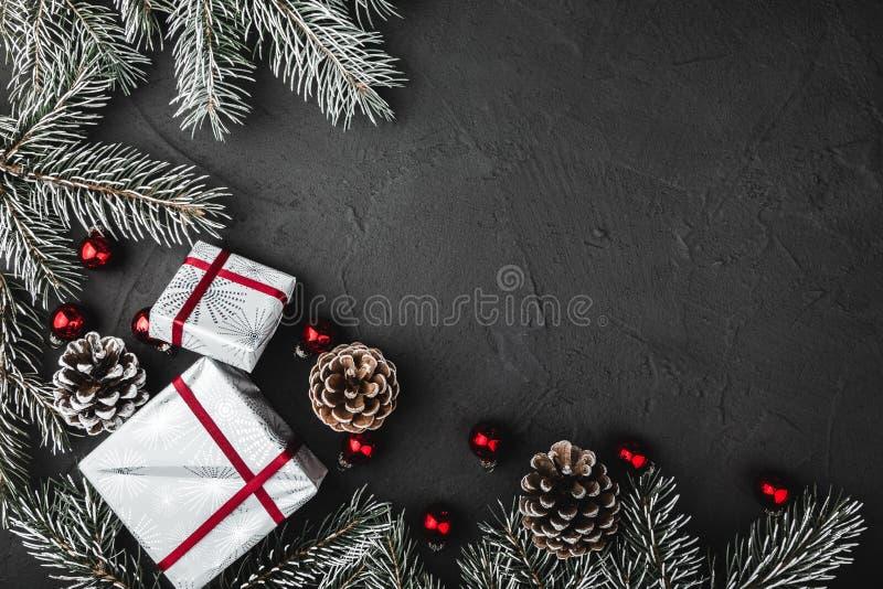 La tomaia, sopra, punto di vista superiore del pino, sempreverde e giocattoli di vetro rossi di Natale, presenta su fondo di piet fotografia stock