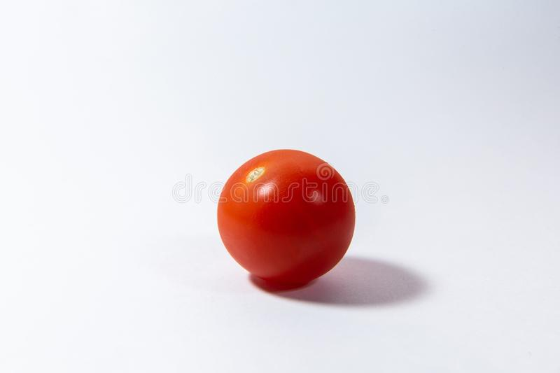 La tomate-cerise rouge se trouve sur un fond blanc photo stock