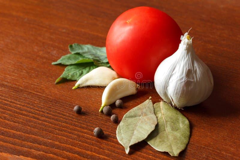 La tomate et l'ail rouges avec des épices sont sur la table photographie stock