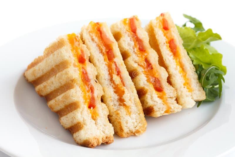 La tomate et le fromage classiques ont grillé le sandwich du plat blanc image libre de droits