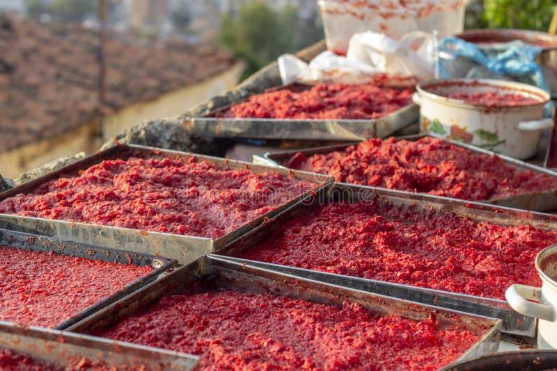 La tomate et le poivre faits main traditionnels de perspective collent le procédé de fabrication au temps de coucher du soleil photographie stock libre de droits