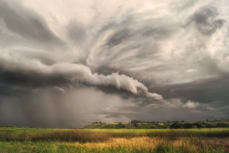 La tormenta del ciclón sobre campos y prados se acerca al valle montañoso Día nublado lluvioso foto de archivo libre de regalías