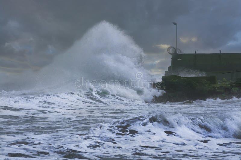 La tormenta del mar agita estrellarse y salpicar contra el embarcadero imagenes de archivo