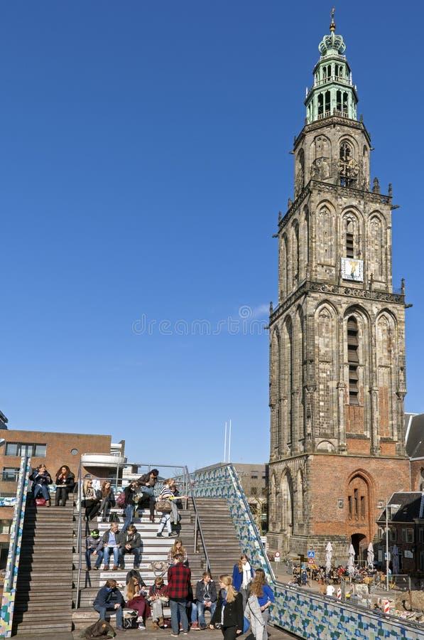 La torre de iglesia Martinitoren, gente goza del sol de la primavera fotos de archivo