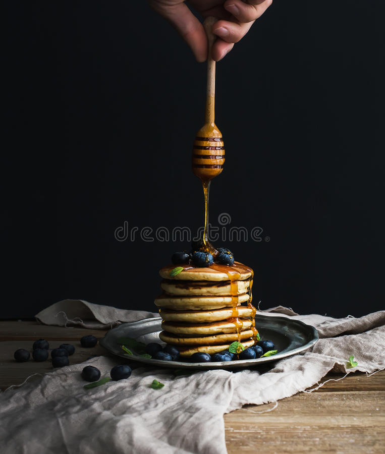 La torre de la crepe con el arándano y la menta frescos en una placa de metal rústica, mano está guardando la miel de colada del  imágenes de archivo libres de regalías