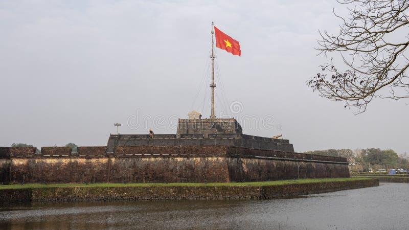 La torre della bandiera di Hue Citadel con la bandiera del volo del Vietnam nel vento immagine stock
