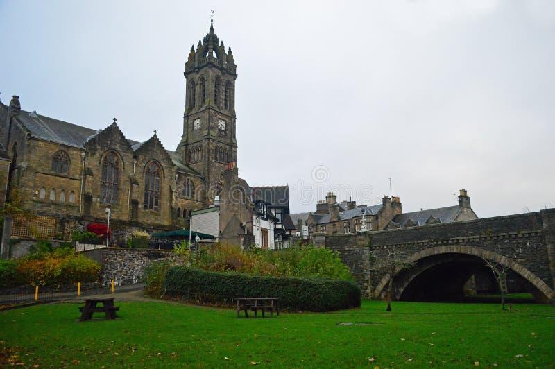 La torre di orologio di vecchia chiesa di parrocchia nei peebles e nel ponte del tweed immagini stock