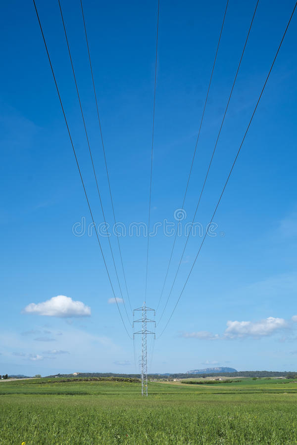 La torre ed il cavo ad alta tensione allineano nella campagna sotto un cielo blu immagine stock libera da diritti
