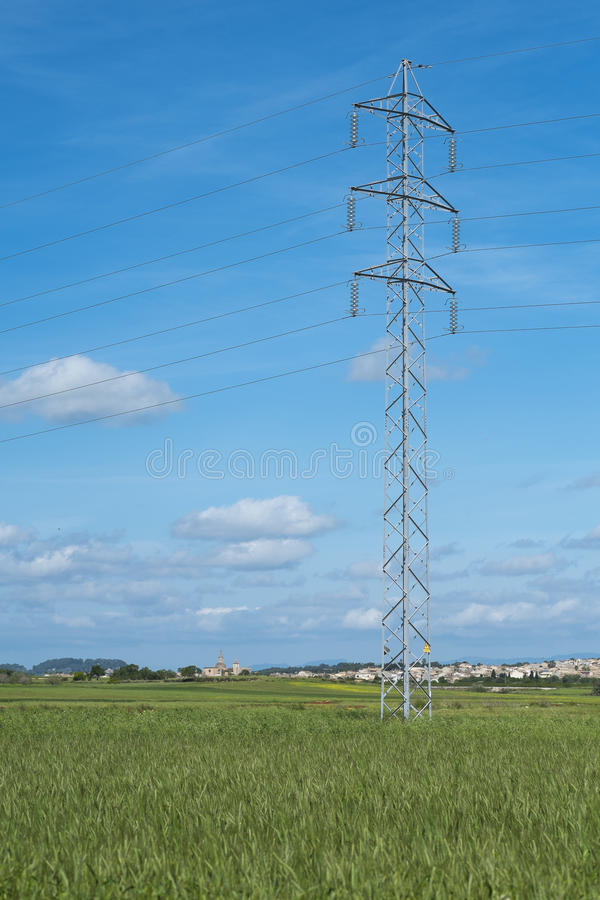 La torre ed il cavo ad alta tensione allineano nella campagna sotto un cielo blu immagini stock
