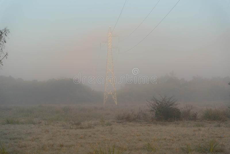 La torre iluminada en medio de la niebla imagen de archivo