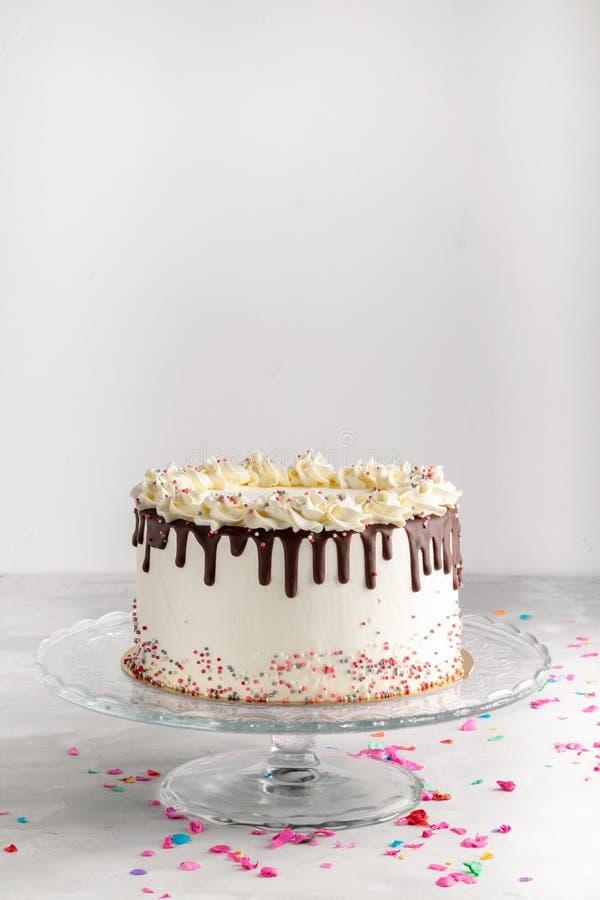 La torta acodada del goteo del cumpleaños con el ganache del chocolate y asperja en un fondo blanco con la decoración del partido fotografía de archivo libre de regalías