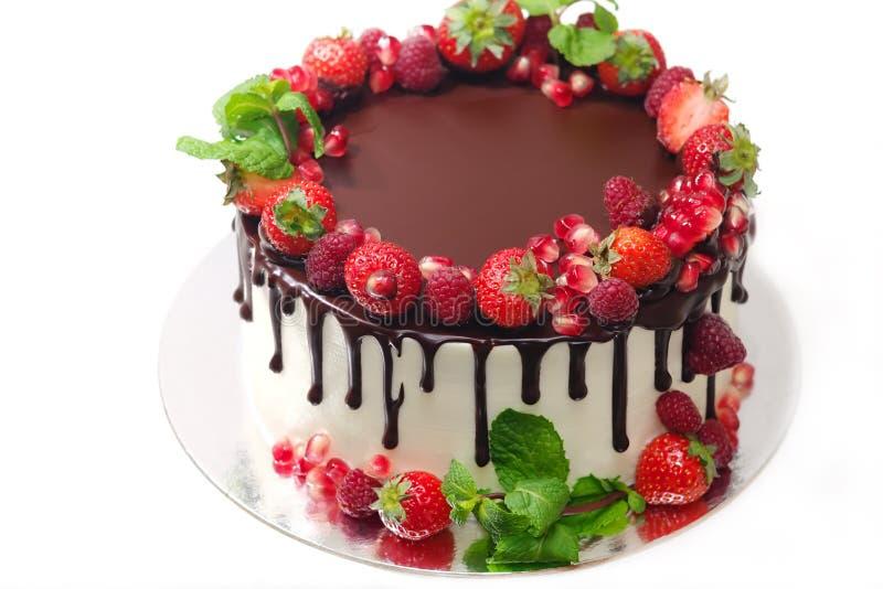 La torta cubierta con las bayas de las hojas de menta de la granada de la fresa de la frambuesa doused con el chocolate en un fon fotografía de archivo