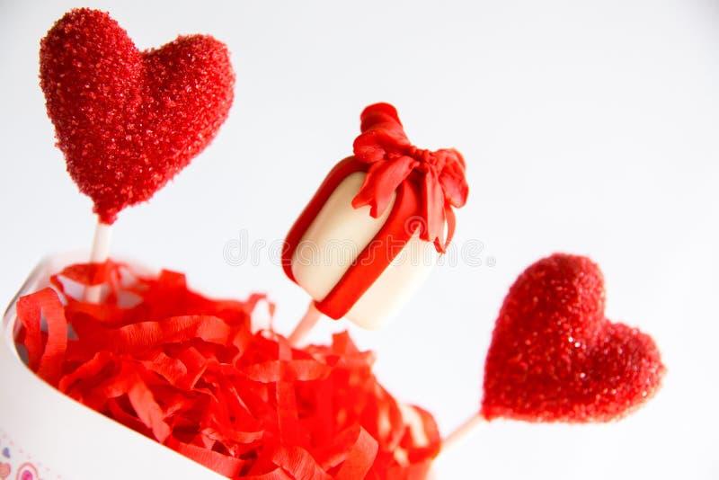 La torta de la caja del corazón y de regalo hace estallar en taza en el fondo blanco Día de tarjeta del día de San Valentín imagenes de archivo