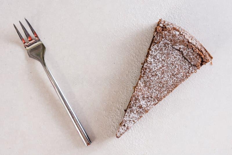 La torta de chocolate con el azúcar en polvo y el metal bifurcan en el fondo de mármol blanco fotografía de archivo libre de regalías