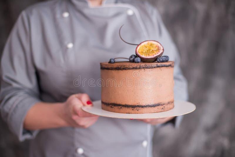La torta de chocolate en un fondo oscuro adornó con la fruta cítrica imagenes de archivo