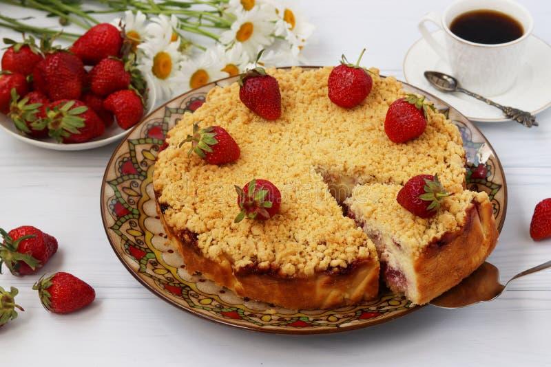 La torta de la cuajada con las fresas con un pedazo de torta cortado está situada en un fondo blanco fotografía de archivo libre de regalías