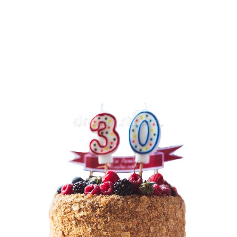 La torta de cumpleaños de la zarzamora de las frambuesas con las velas numera 30 en el fondo y el copyspace blancos para su texto fotos de archivo libres de regalías