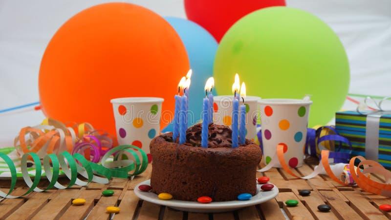 La torta de cumpleaños del chocolate con un azul mira al trasluz el burning en la tabla de madera rústica con el fondo de los glo imagenes de archivo
