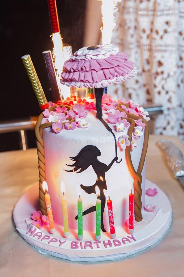 La torta de cumpleaños del ` s de la muchacha Un paraguas en su mano sobre la torta Cumpleaños fotos de archivo libres de regalías