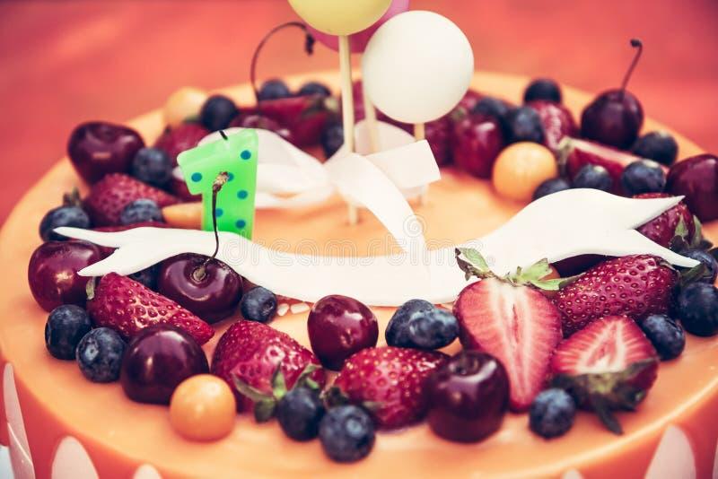 La torta de cumpleaños para los niños va de fiesta con las bayas y el esmalte anaranjado del descenso en fondo anaranjado fotos de archivo libres de regalías