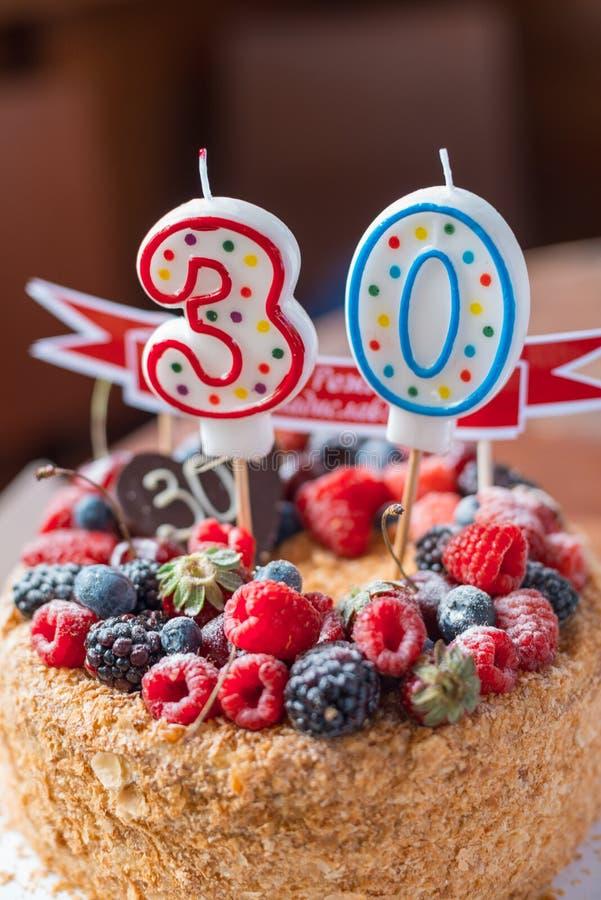 La torta de cumpleaños de la zarzamora de las frambuesas con las velas numera 30 en fondo defocused tiro macro del foco selectivo foto de archivo