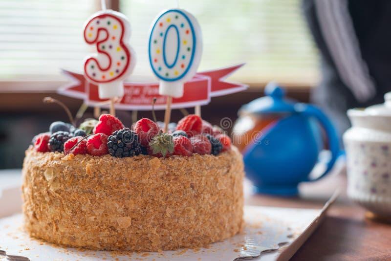 La torta de cumpleaños de la zarzamora de las frambuesas con las velas numera 30 en fondo defocused tiro macro del foco selectivo imágenes de archivo libres de regalías