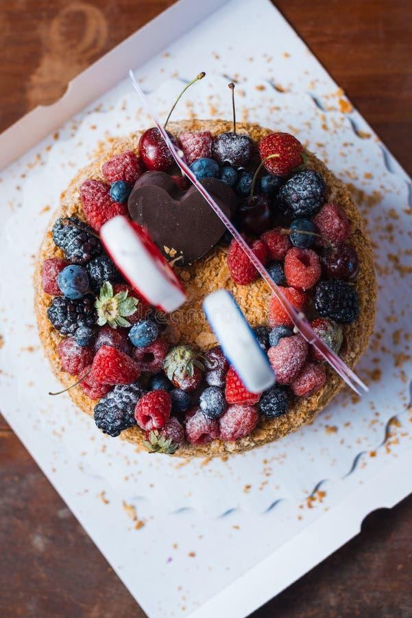 La torta de cumpleaños de la zarzamora de las frambuesas con las velas numera 30 en fondo defocused tiro macro del foco selectivo foto de archivo libre de regalías