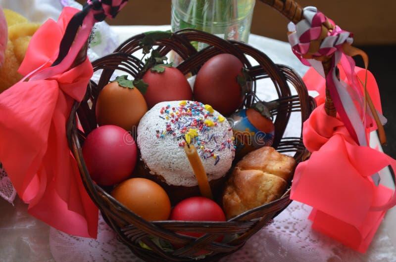 La torta de Pascua con los huevos pintados miente en una cesta del marrón oscuro foto de archivo libre de regalías
