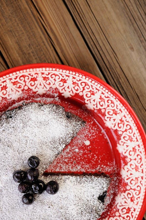 La torta del cioccolato con il mirtillo e lo zucchero a velo ha tagliato in piatto rosso fotografia stock libera da diritti