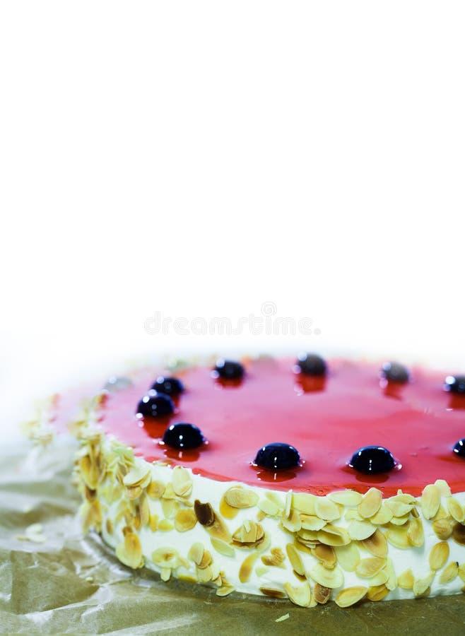 La torta di compleanno con il ciliegio dolce, gelatina rossa, mandorla si sfalda Fondo bianco, spazio della copia Modello di prog immagini stock