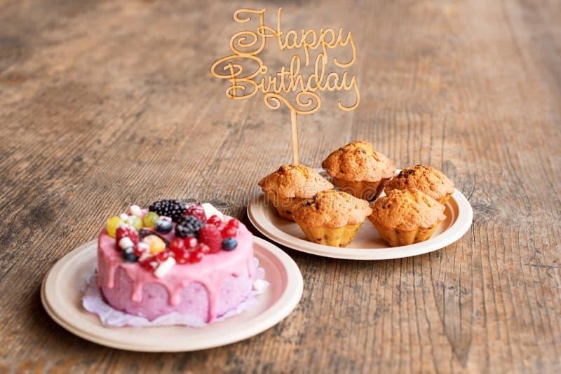 La torta di compleanno ed i muffin con il saluto di legno firmano su fondo rustico Di legno canti con il buon compleanno delle le fotografie stock libere da diritti