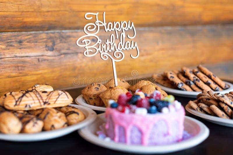 La torta di compleanno ed i muffin con il saluto di legno firmano su fondo rustico Di legno canti con il buon compleanno delle le immagine stock