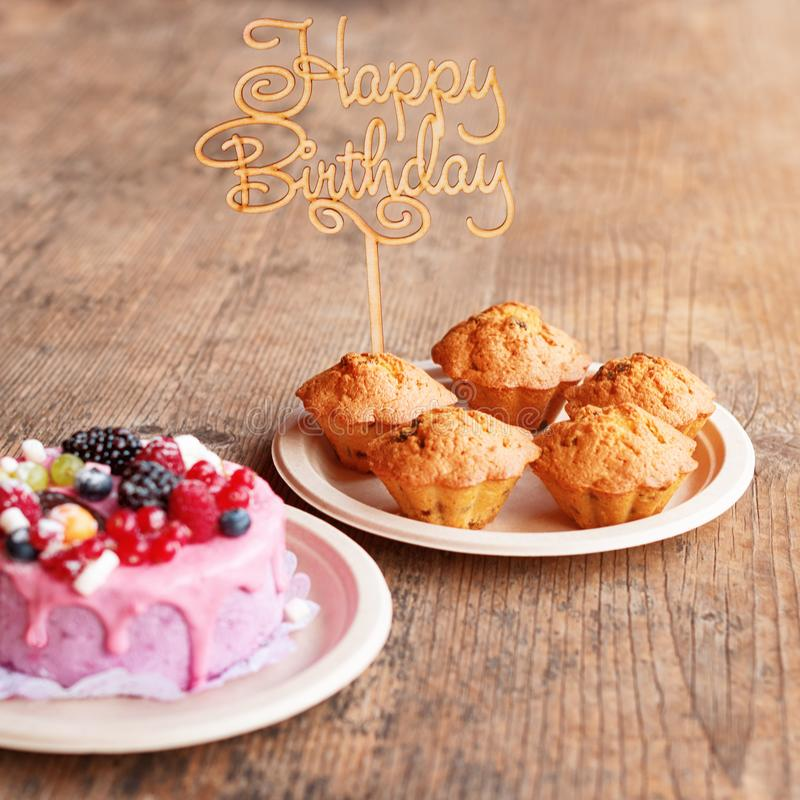 La torta di compleanno ed i muffin con il saluto di legno firmano su fondo rustico Di legno canti con il buon compleanno delle le fotografia stock libera da diritti