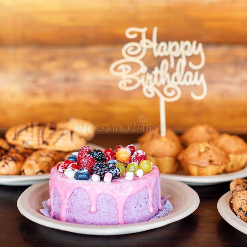 La torta di compleanno ed i muffin con il saluto di legno firmano su fondo rustico Di legno canti con il buon compleanno delle le fotografia stock