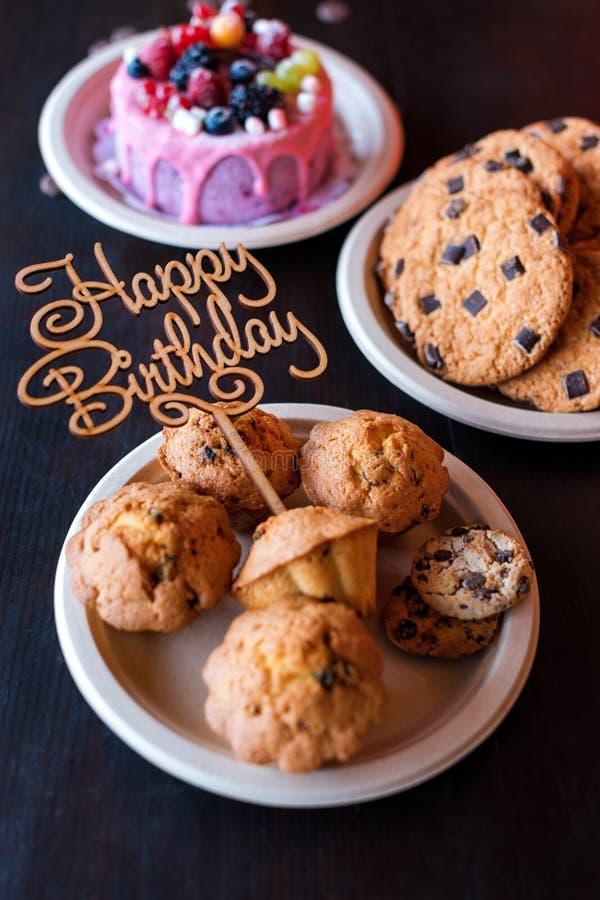 La torta di compleanno ed i muffin con il saluto di legno firmano su fondo rustico Di legno canti con il buon compleanno delle le immagini stock libere da diritti