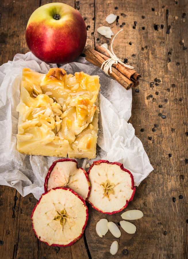 La torta di mele nel bianco ha sgualcito la carta con cannella e le mandorle immagine stock