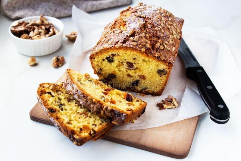 La torta hermosa apetitosa del pan o del pan con las nueces, las frutas secadas cortó en pedazos en una tabla de cortar de madera imagenes de archivo