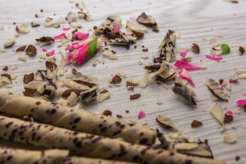 La torta impanata ha riempito di varietà crema della fragola e del cioccolato di sapori su un fondo di legno bianco immagini stock libere da diritti