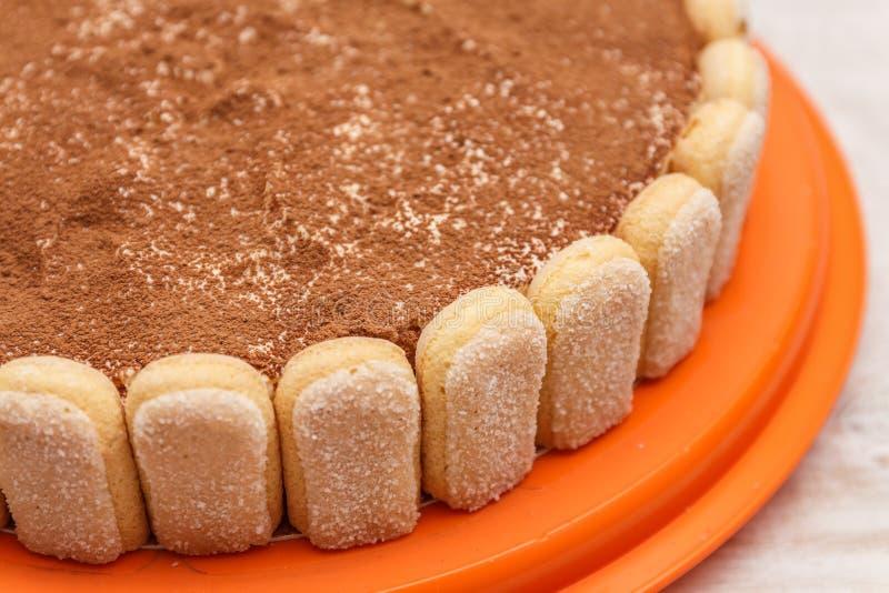 La torta redonda del tiramisu en la tabla de madera blanca asperja con el powd del cacao fotos de archivo