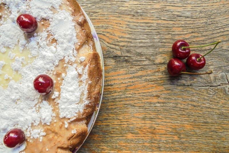 La torta sacada el polvo con el azúcar en polvo y adornada con las bayas de las cerezas dulces de la cereza dulce tres miente cer imagen de archivo