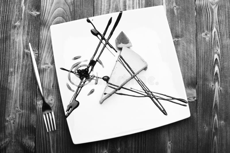 La torta sirvió en restaurante, pastelería o café Postre con las líneas del chocolate, los arándanos y la decoración del triángul fotos de archivo libres de regalías