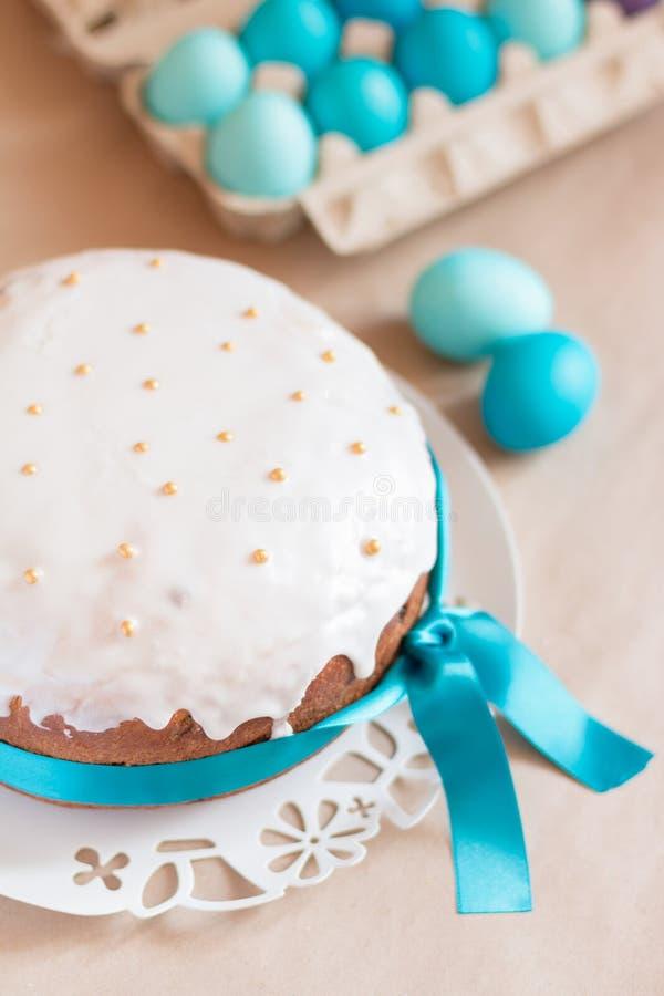 La torta y el azul tradicionales de Pascua del ruso colorearon los huevos en el cartón de huevos de papel fotografía de archivo
