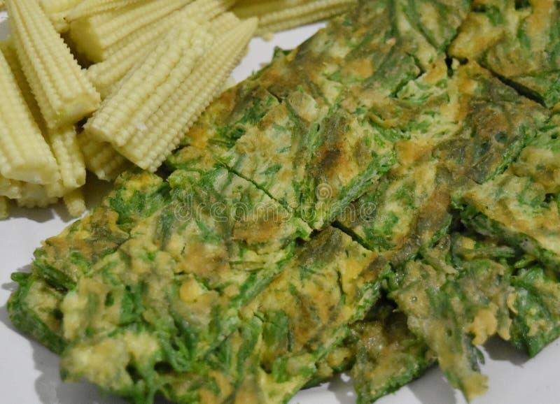 La tortilla frió con el acacia cha-OM con maíz joven hervido imagen de archivo
