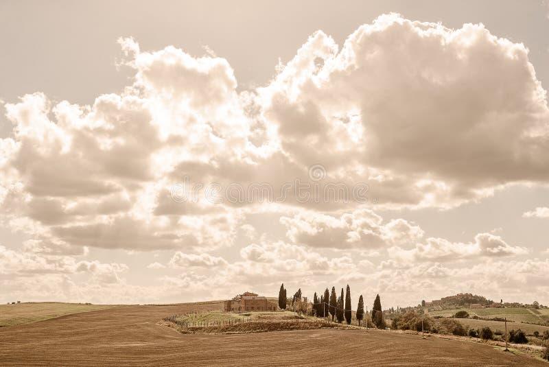 La Toscana - una proprietà del paese si siede fra la Rolling Hills vicino a Asciano immagini stock libere da diritti