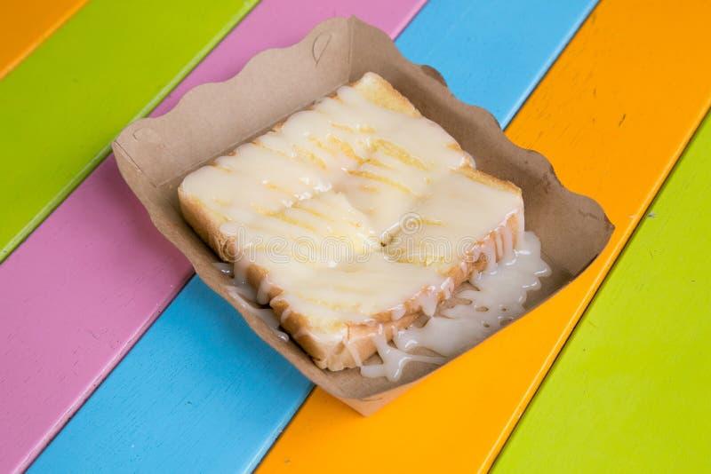 La tostada remató con leche condensada azucarada en un plato de papel en una tabla de madera fotografía de archivo libre de regalías
