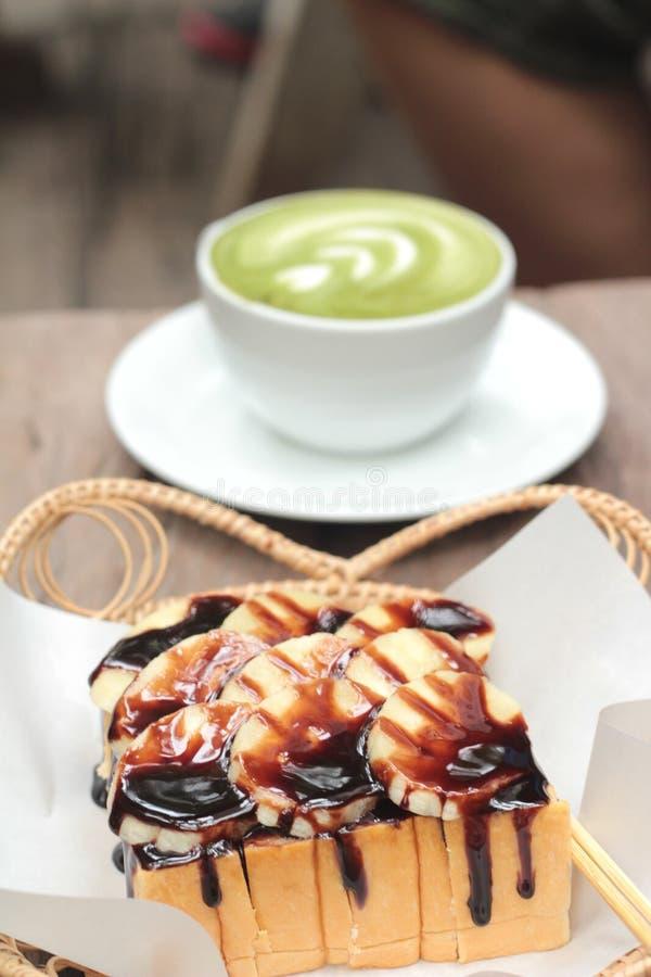 La tostada remató con los plátanos y el chocolate - té con leche verde imagen de archivo libre de regalías