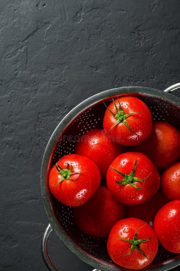 La totalité crue a lavé des tomates-cerises dans une passoire sur le fond noir gris-foncé avec l'espace de copie Vue sup?rieure photo stock