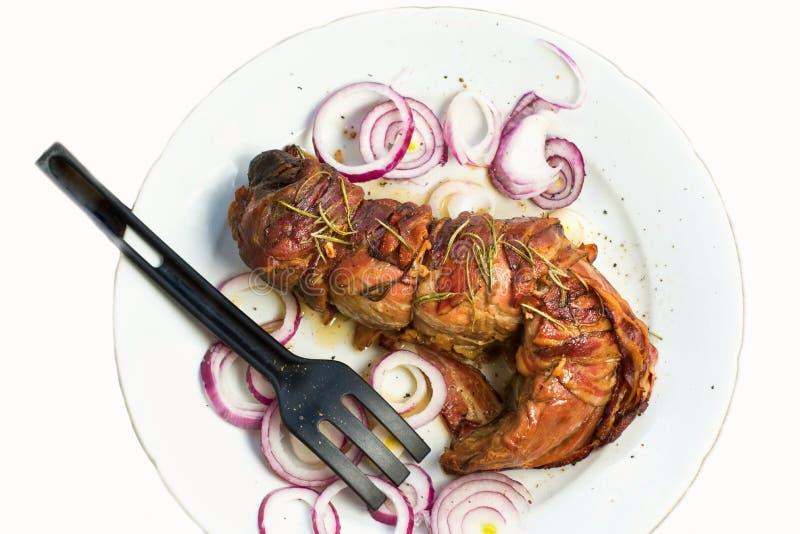 La totalité a rôti le filet de porc avec le cercle de lard et d'oignon image libre de droits