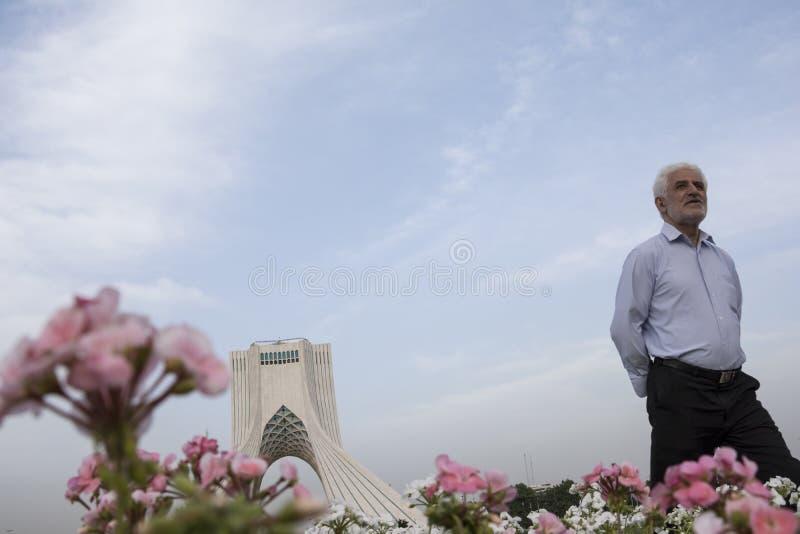 La tour d'Azadi derrière la fleur rose et blanche de cranesbill de géranium photos libres de droits