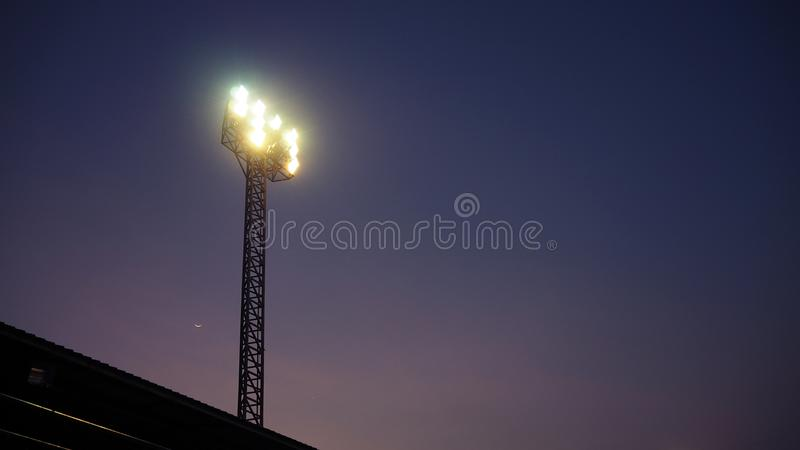 La tour de projecteur de stade au-dessus du terrain de football à la nuit images stock